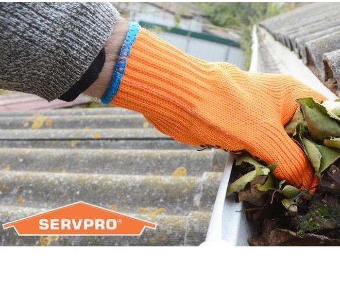 SERVPRO representative cleaning out the rain gutters